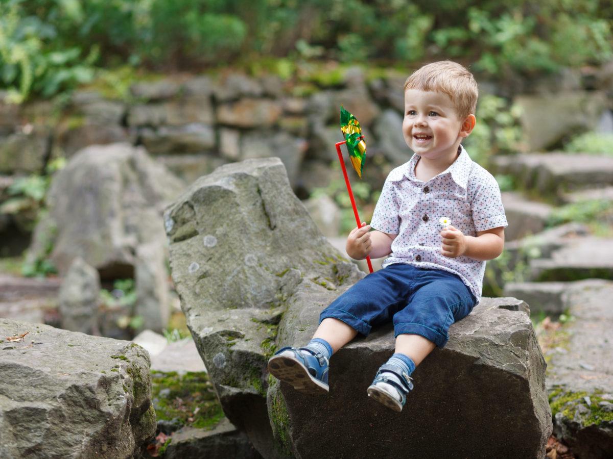 child enjoying boulder in yard