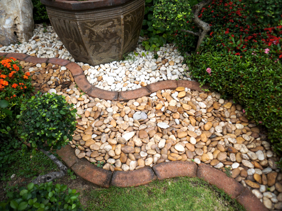 Curved dry creek bed with brick border and grass