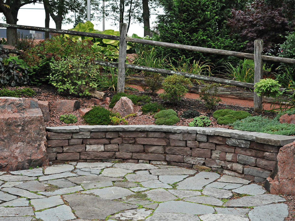 flagstone patio with rock wall and garden