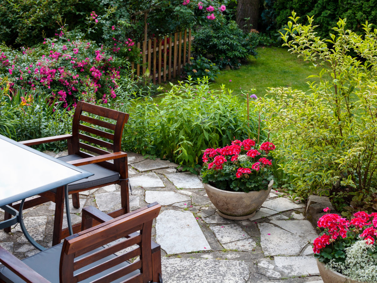 Flagstone patio with potted plants and dining set