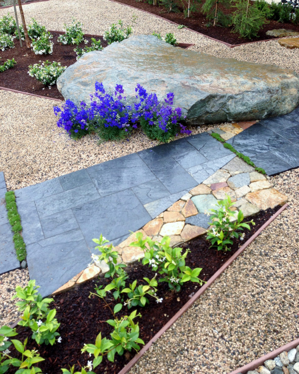 Zen garden flagstone pathway with boulder