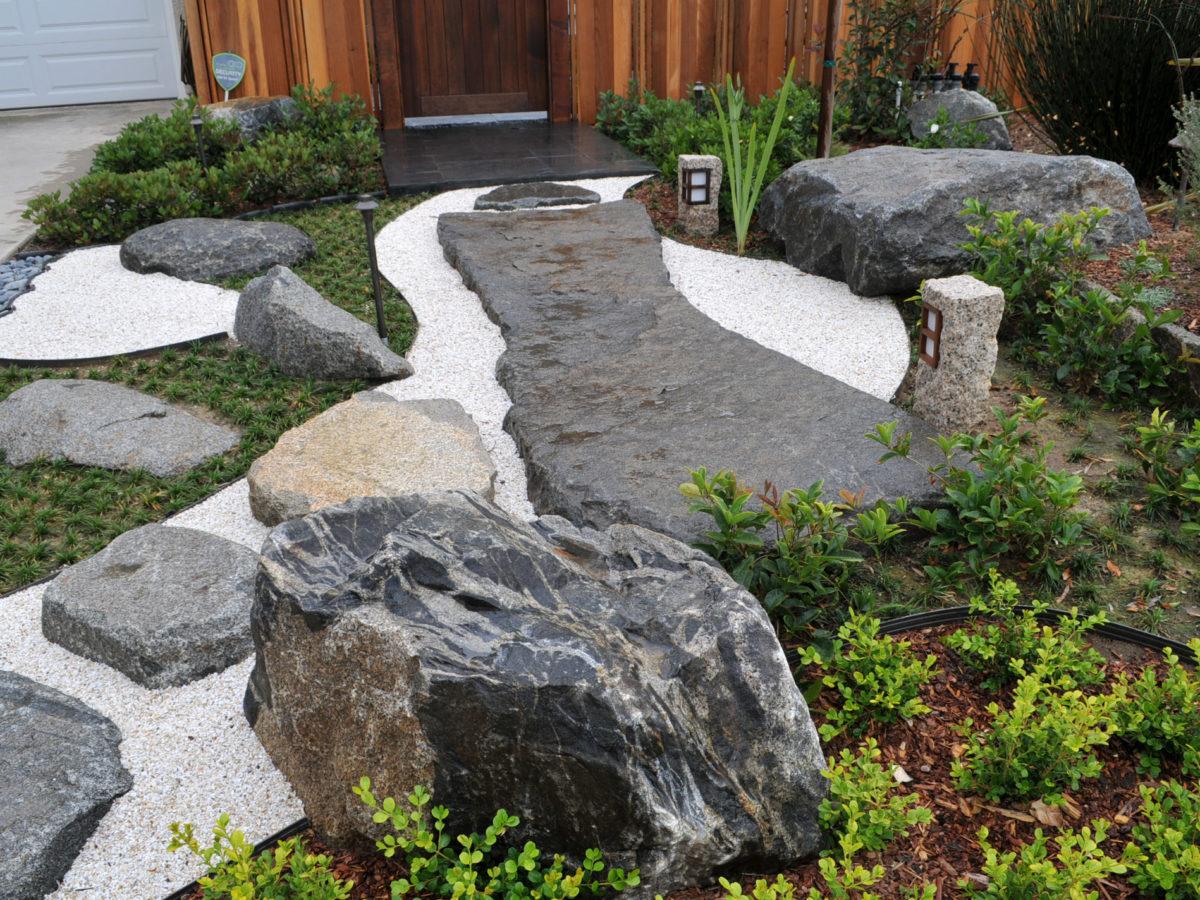 Rock slab pathway with white sand in zen garden