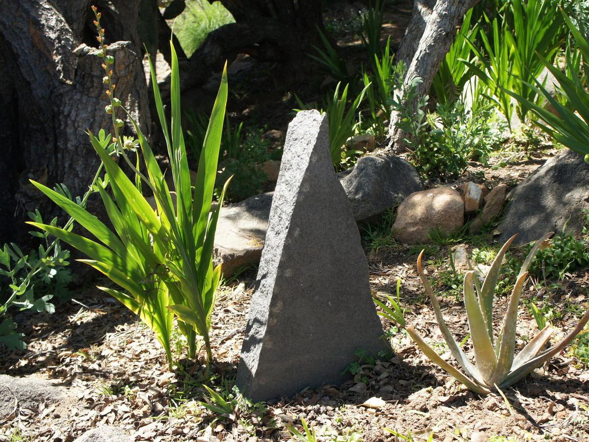 Carved stone piece in mosaic rock garden