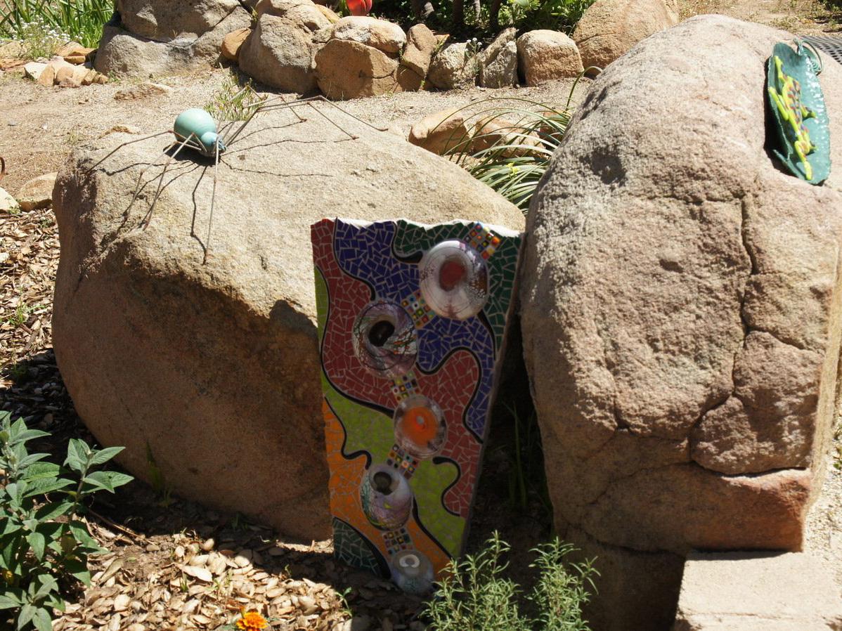 Small mosaic rock garden art piece next to boulder