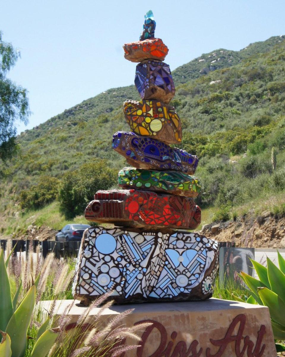 Stacked mosaic rock art piece in yard